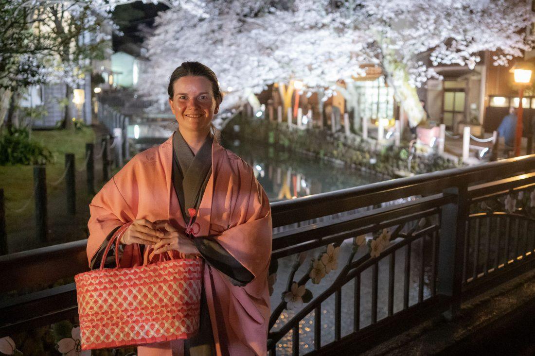 Erin en kimono par le canal bordé de fleurs de cerisier à Kinosaki Onsen